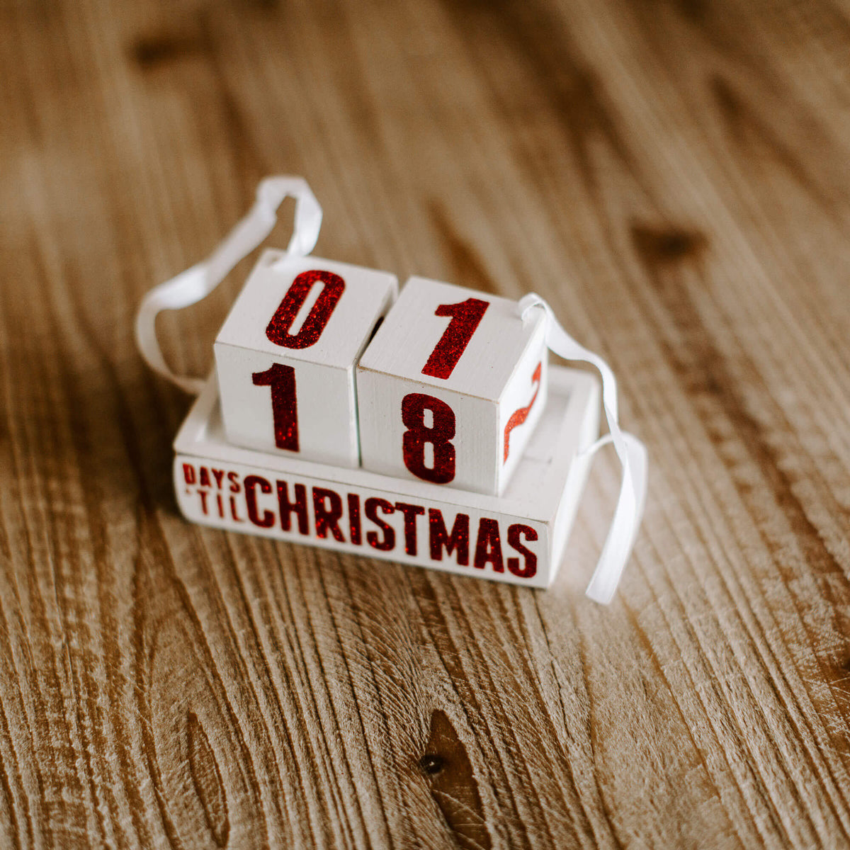 A small ornament with white ribbon and red glitter words that read Days 'til Christmas, numbered blocks to countdown the days