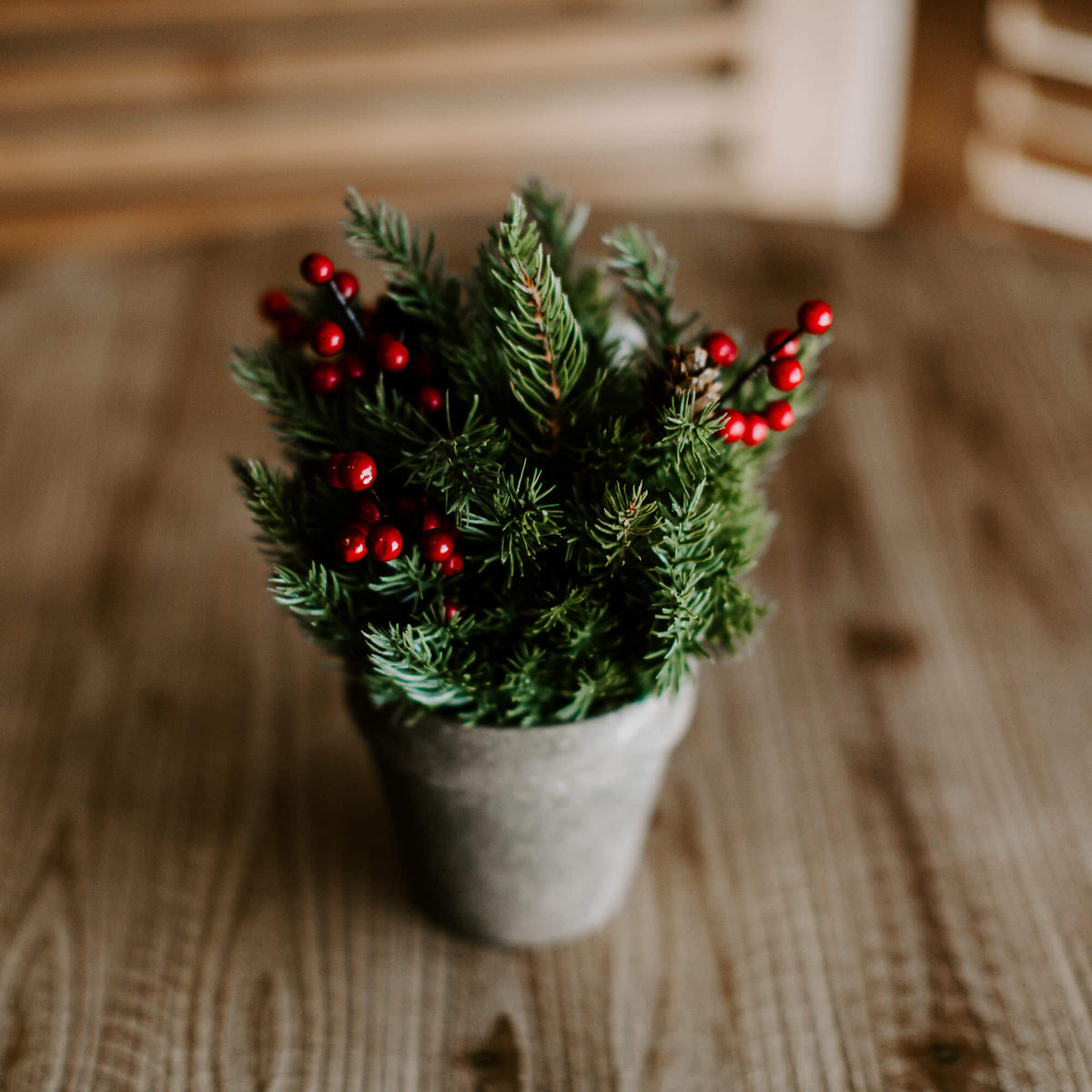 A 9 and half inch faux spruce sphere with tiny pinecones and red berry accents, inside a rustic gray pot for holiday tabletop decorating