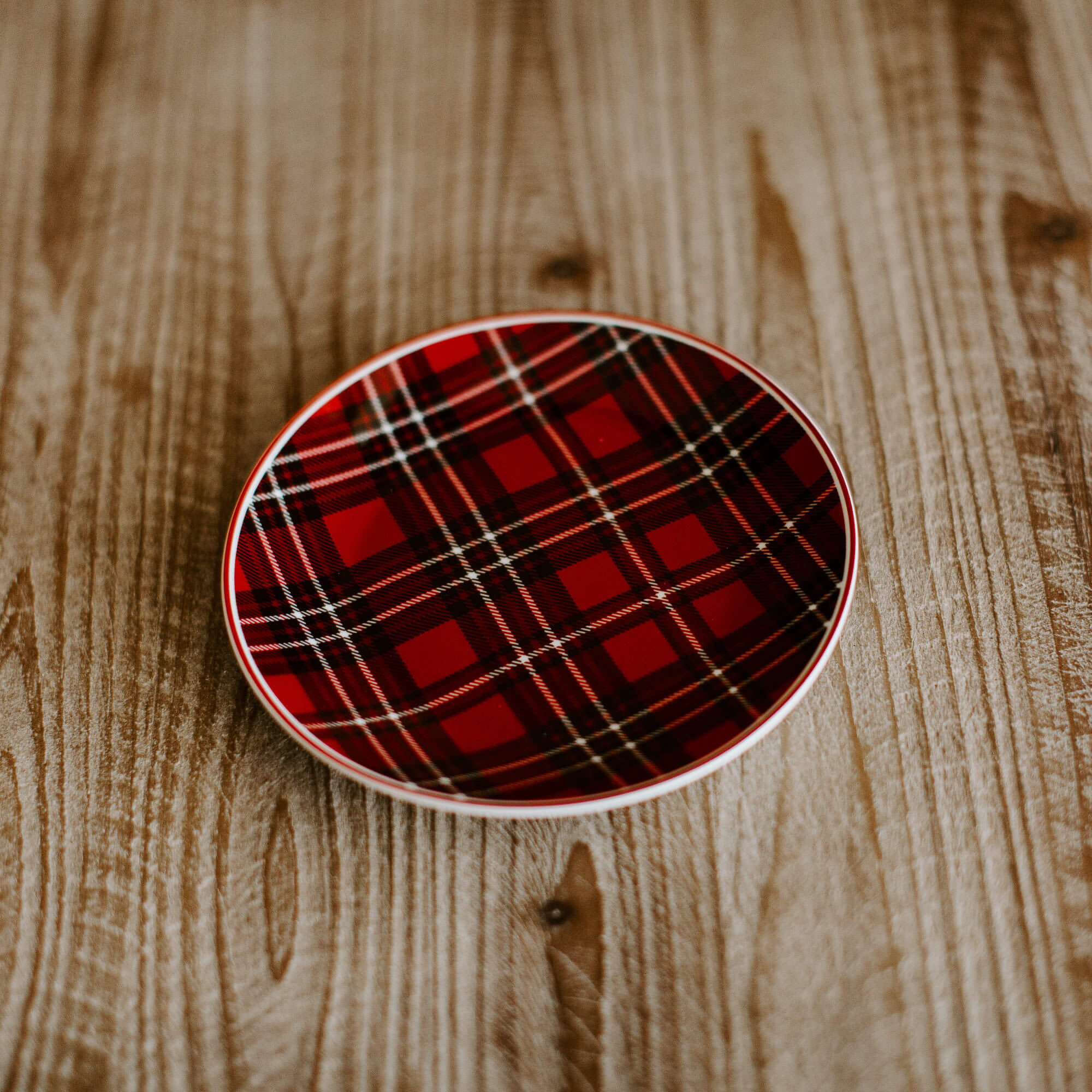 A small 6 inch plate in a red and black plaid pattern for the holiday table
