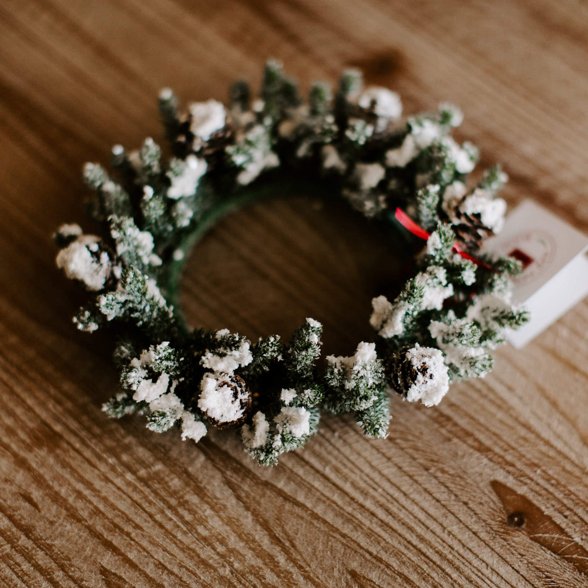 A small 4 inch diameter faux pine and pinecone wreath with clumps of faux snow for holiday decorating