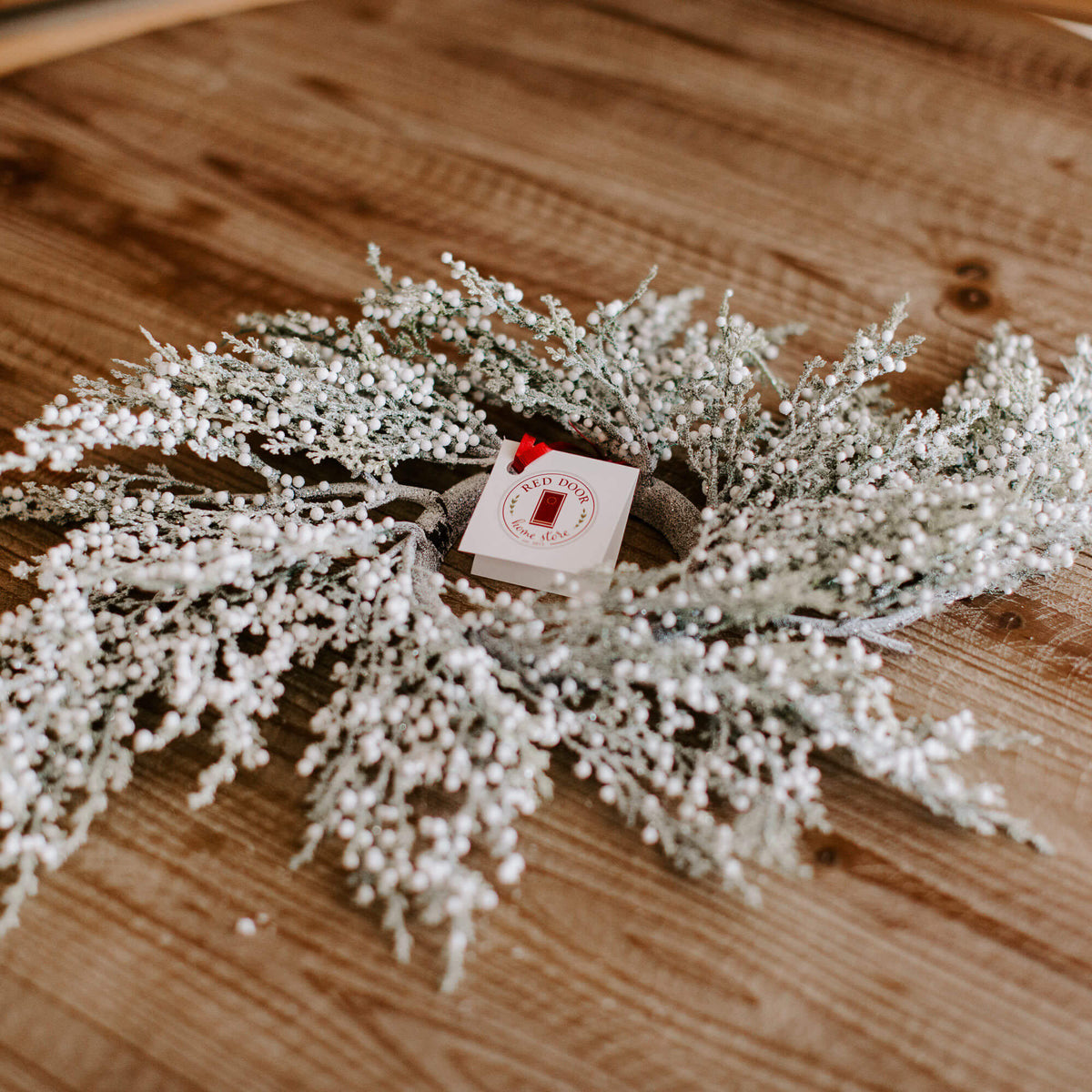 A 23 inch faux frosted cedar ring with loads of tiny white berries resting on a table for winter decorating