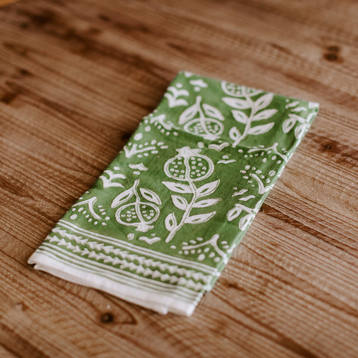 green and white patterned dish towel folded up on a countertop