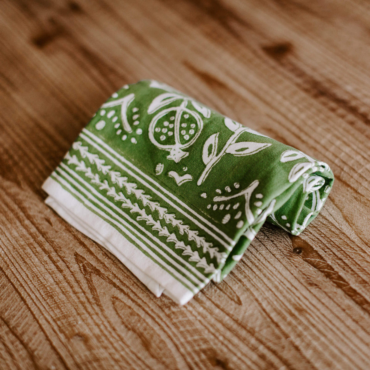 green and white patterned dish towel rolled up on a tabletop