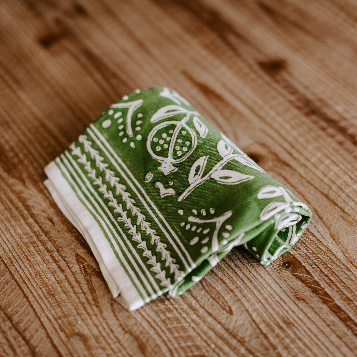 green and white patterned dish towel rolled up on a table