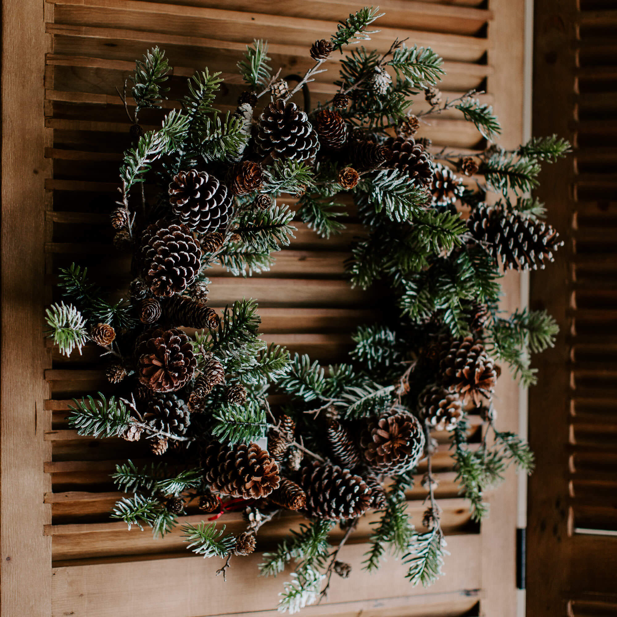 A full and lush 28 inch diameter, natural-looking faux spruce wreath loaded with pinecones of different sizes all dusted in faux snow perfect for holiday decorating