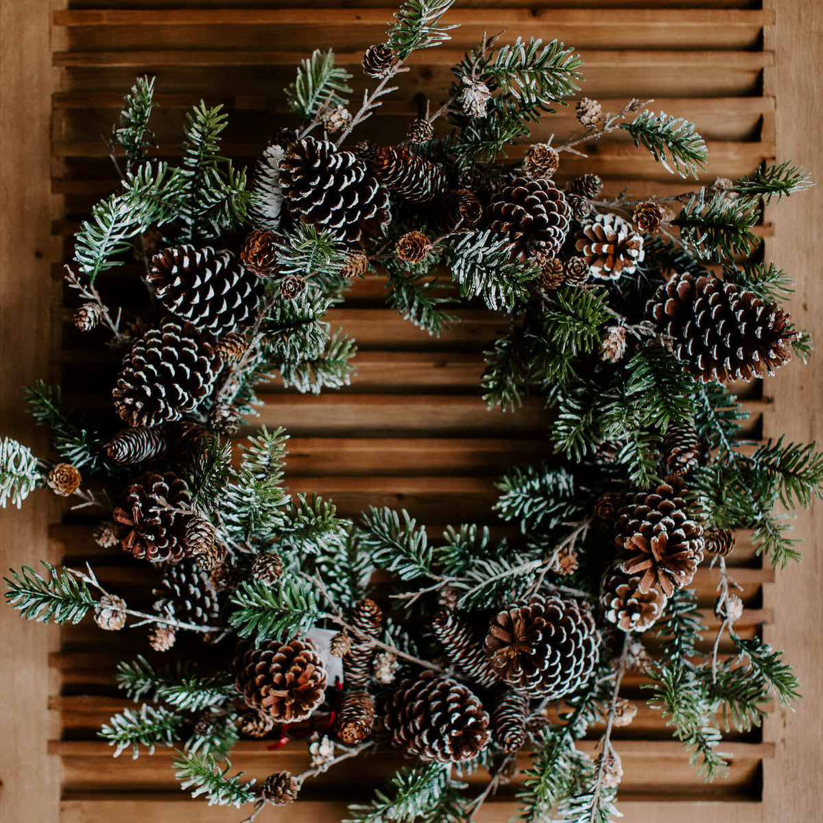 A full and lush 28 inch diameter, natural-looking faux spruce wreath loaded with pinecones of different sizes all dusted in faux snow perfect for holiday decorating  Edit alt text