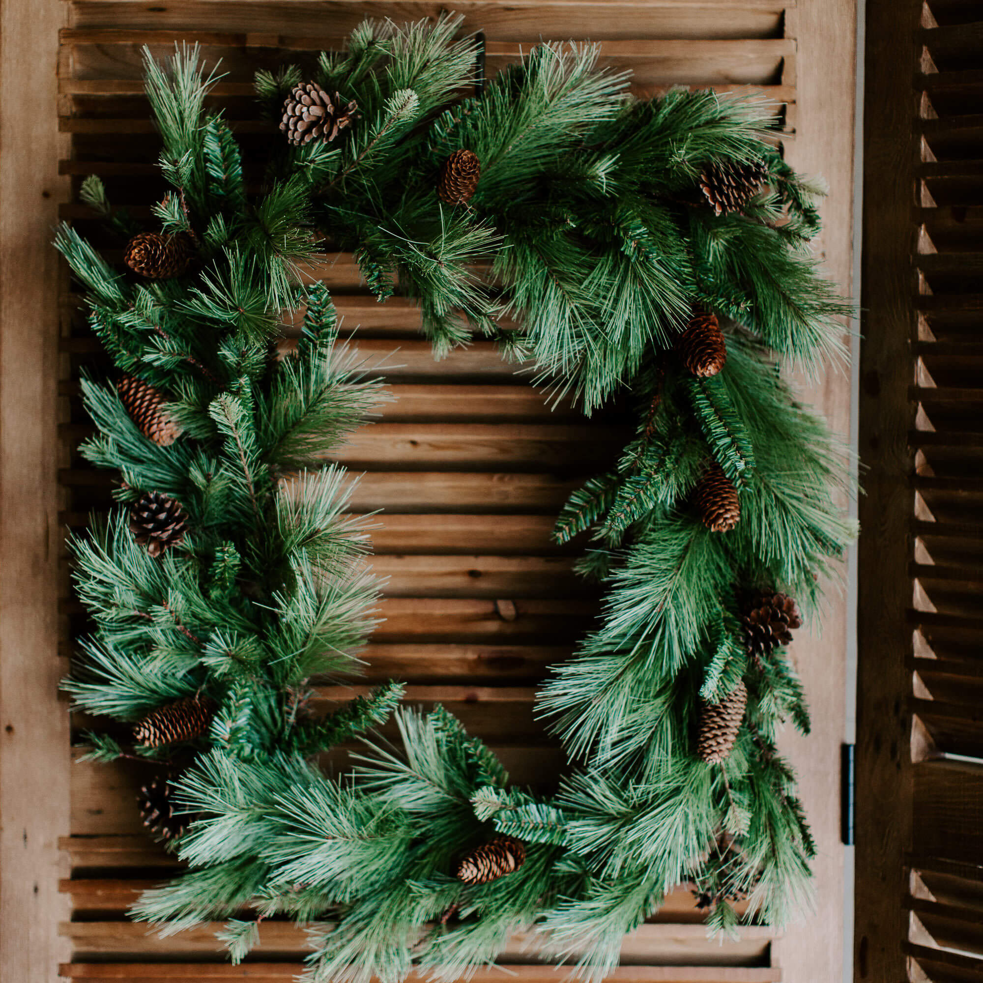 A 22 inch by 30 inch rectangular faux green pine wreath with natural pinecones adorn a front door for winter greetings