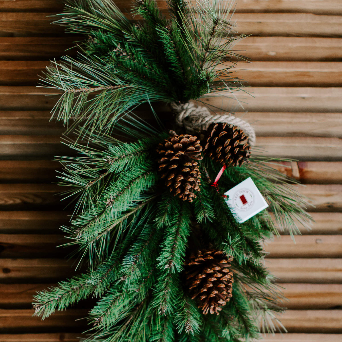 The closeup details of a grand 40 inch long faux pine drop or swag wrapped in a natural rope and adorned with pinecones for a winter front door decor