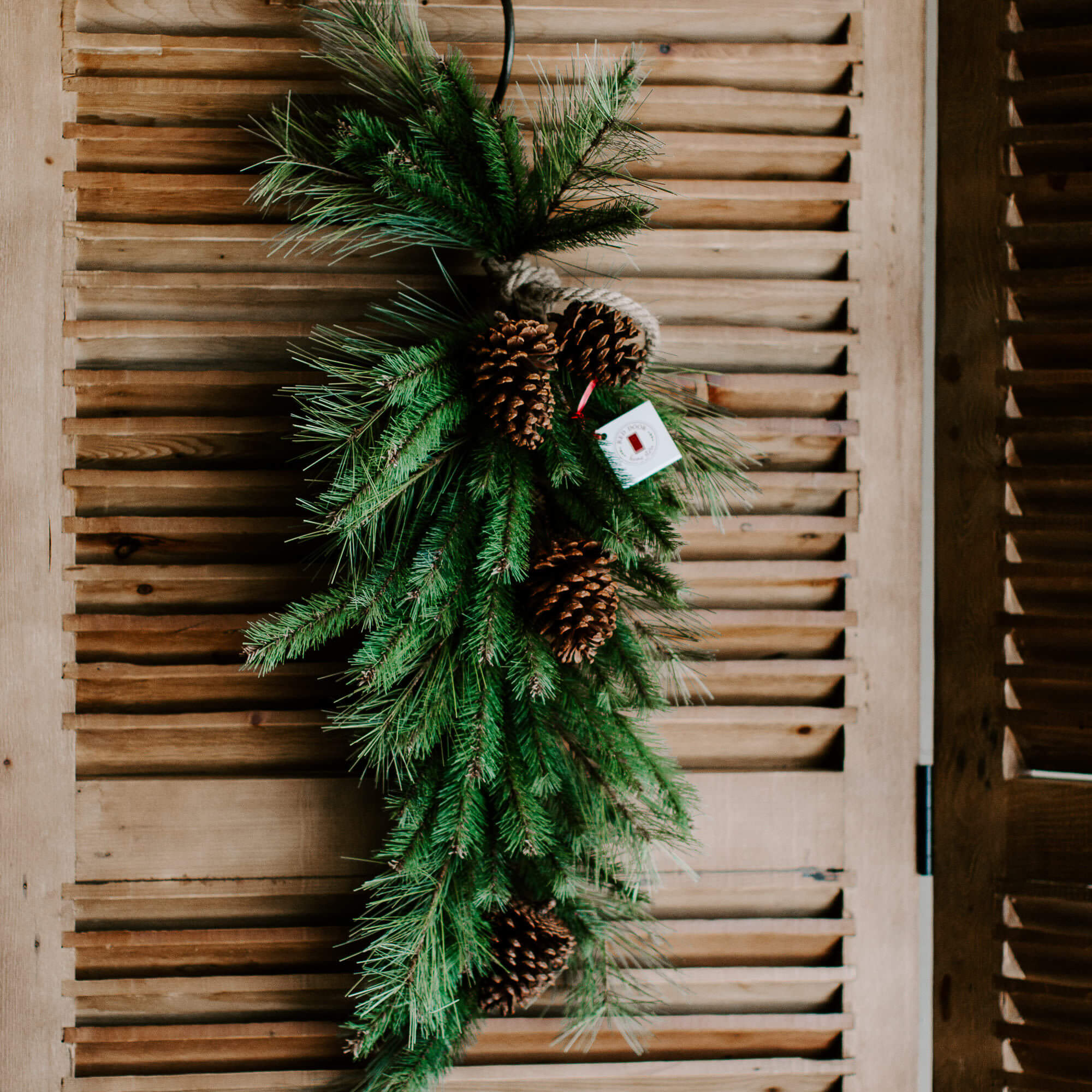 A grand 40 inch long faux pine drop or swag wrapped in a natural rope and adorned with pinecones for a winter front door decor