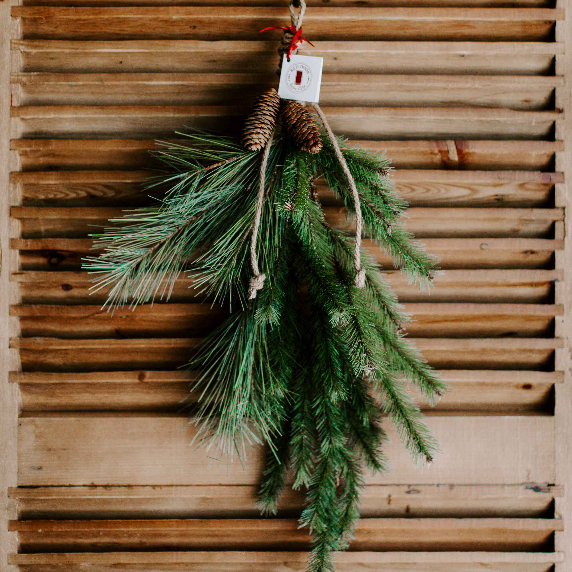 A 28 inch long faux pine swag with a mix of long and short pine needles, tied at the top with a natural twine and 2 pinecones hung on a front door for winter decorating