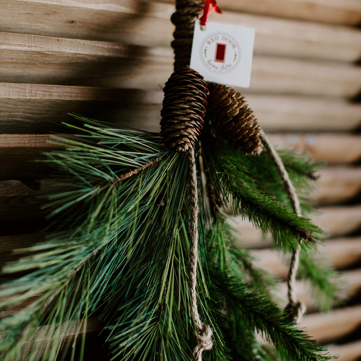 "The closeup details of the pinecones and natural twine wrapped around the top of this 28"" faux greenery drop or swag"