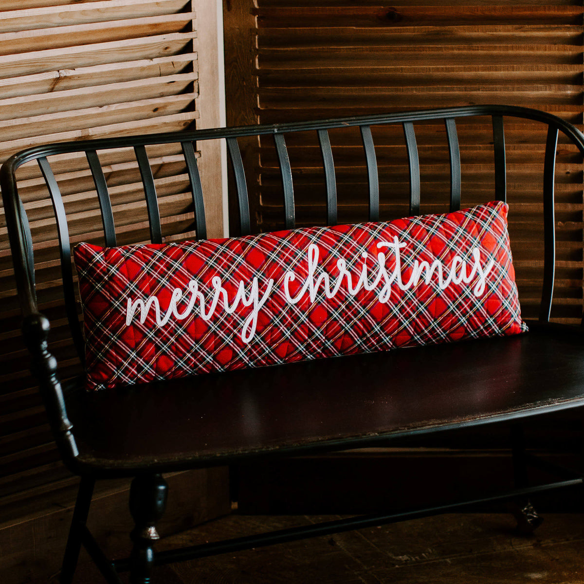 "36 inch long red tartan pillow with script ""Merry Christmas"" in white, resting on a black hallway bench"