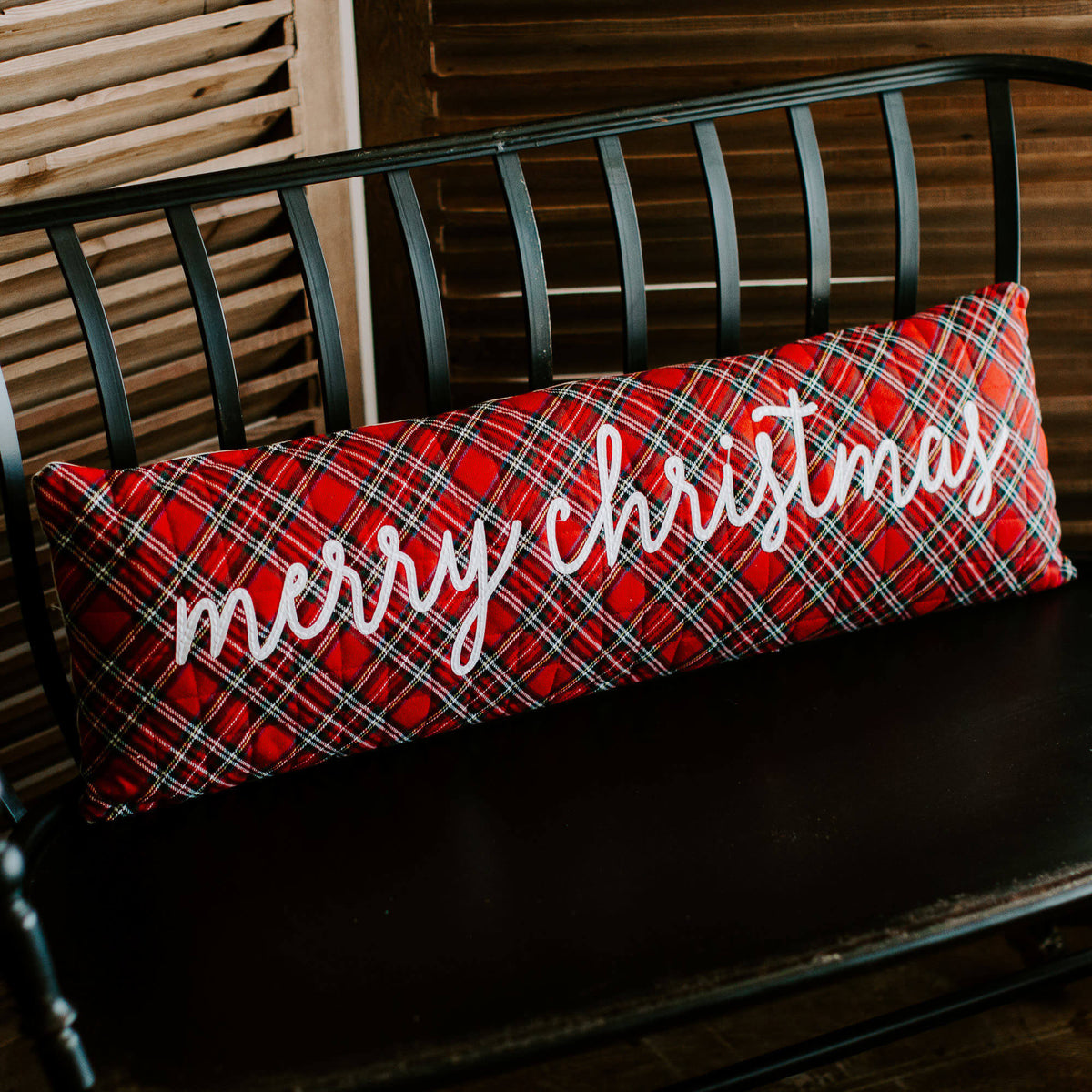 "36 inch long red tartan pillow with script ""Merry Christmas"" in white, resting on a black entryway bench"