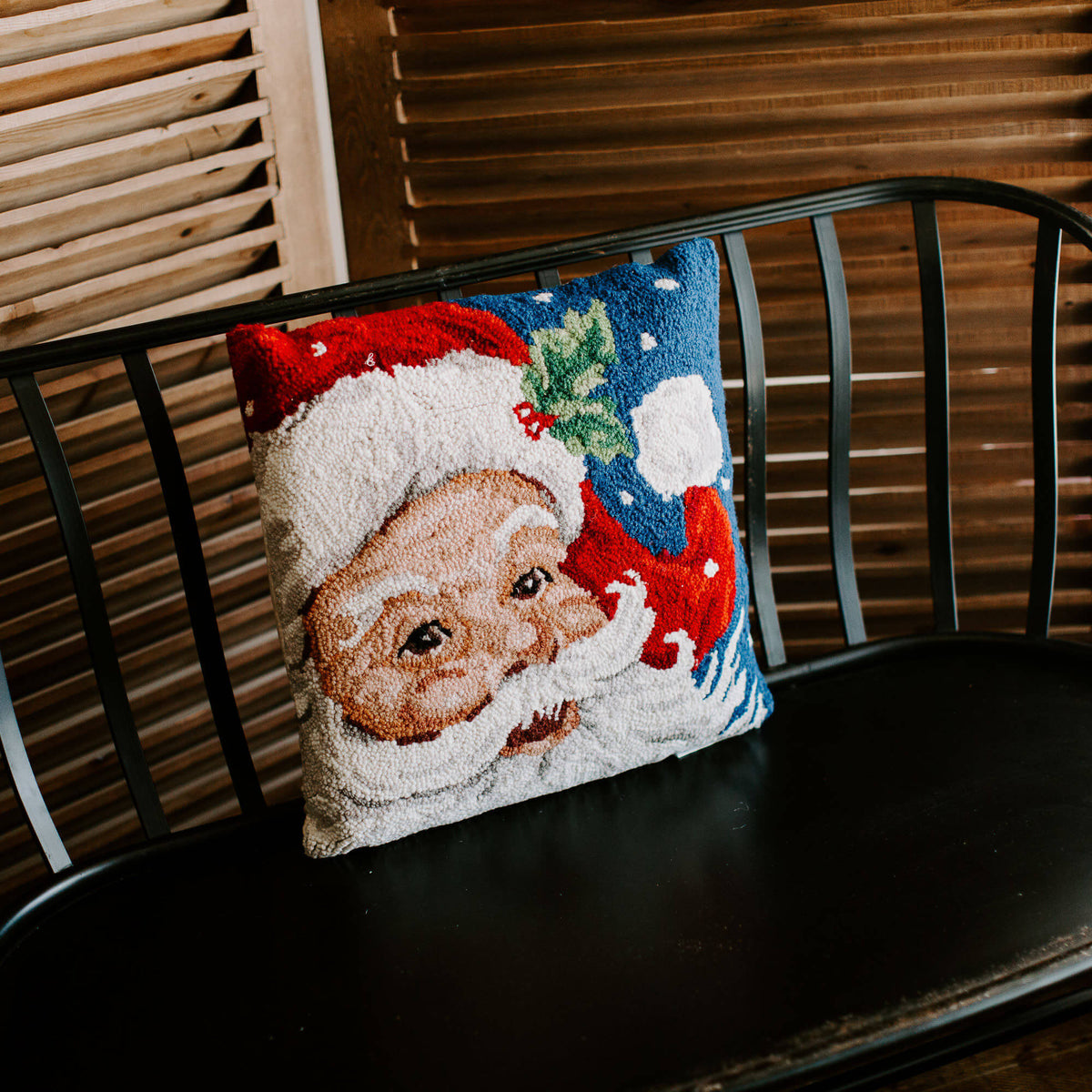 Vintage-looking Santa pillow with blue sky background, resting on a black bench