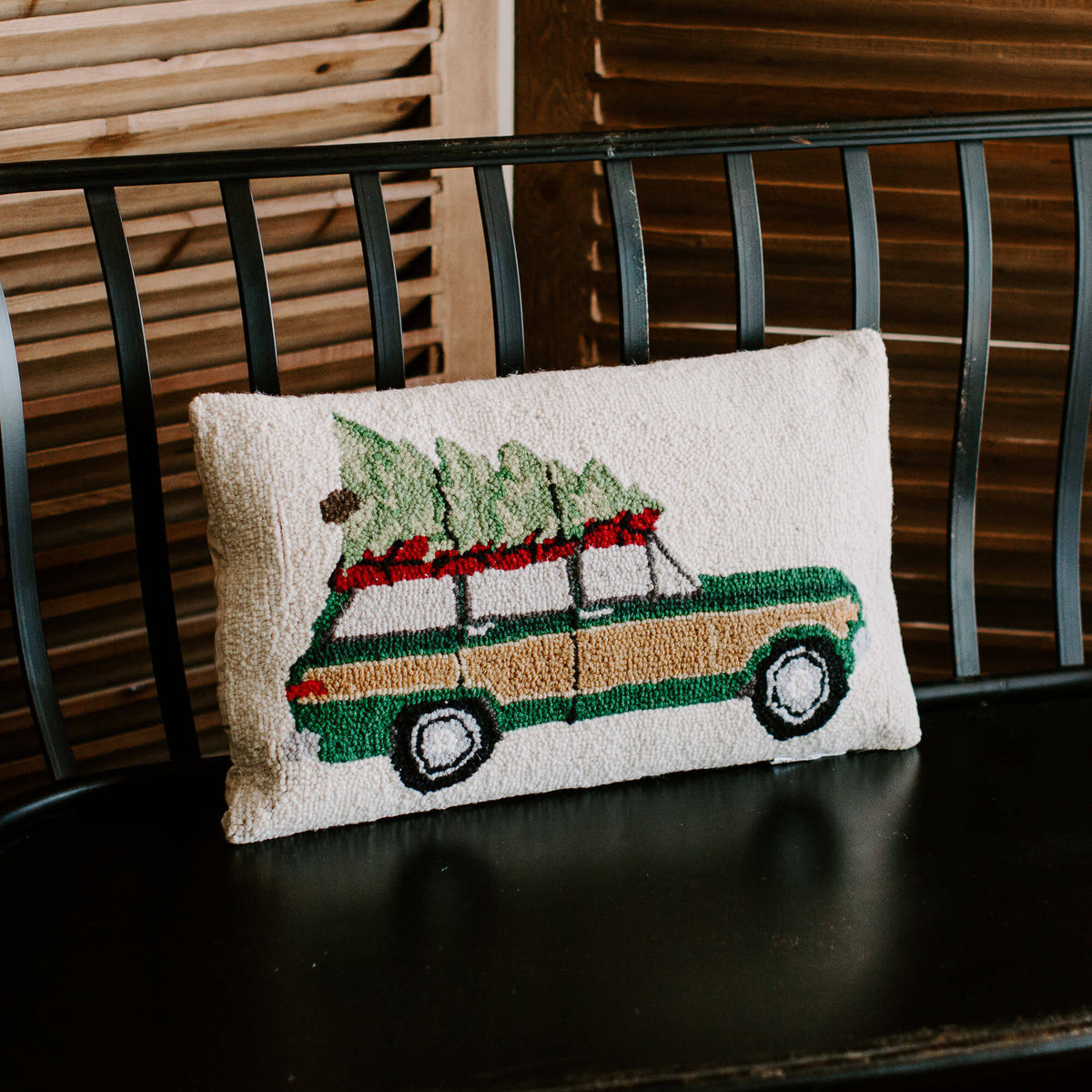 Vintage wool loop pillow with an old jeep carrying a Christmas tree on top, resting on a black bench