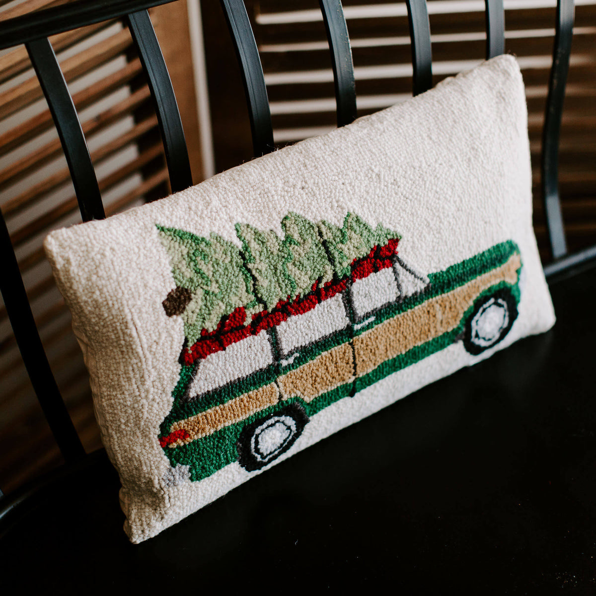 close up detail of a vintage wool loop pillow with an old jeep carrying a Christmas tree on top, resting on a black bench