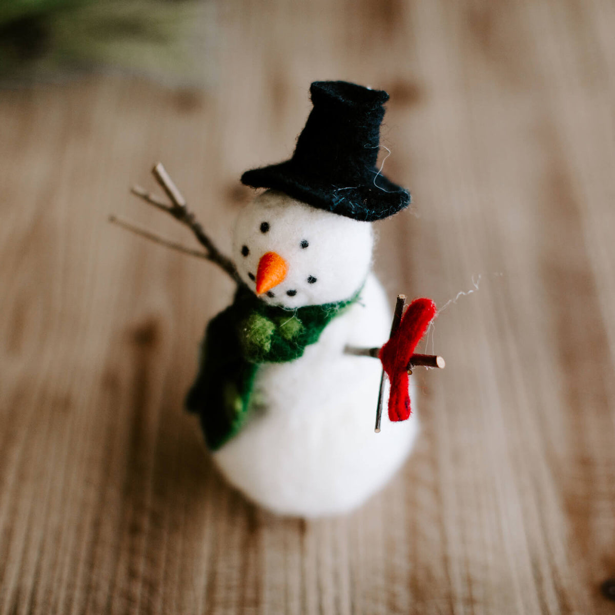 7 and half inch tall wool snowman with real twig arms, holding a red wool heart and wearing a green scarf and black hat, resting on a table with Christmas decor