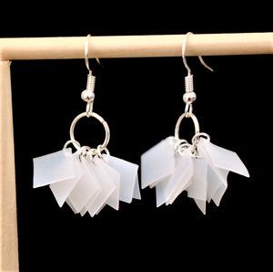 Upcycled earrings made from milk bottles cut into about 10 exact squares all dangling from one hoop.