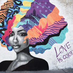 A black and while drawing of an african woman with massive colourful hair with lots of different designs.  Love is Colour is written on the wall beside her.