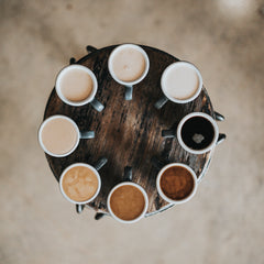 8 cups of coffee in a circle all different shades representing the diversity of colour of people on this planet.