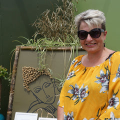 Picture of Rebecca Agnew with a garden bamboo picture of a buddha