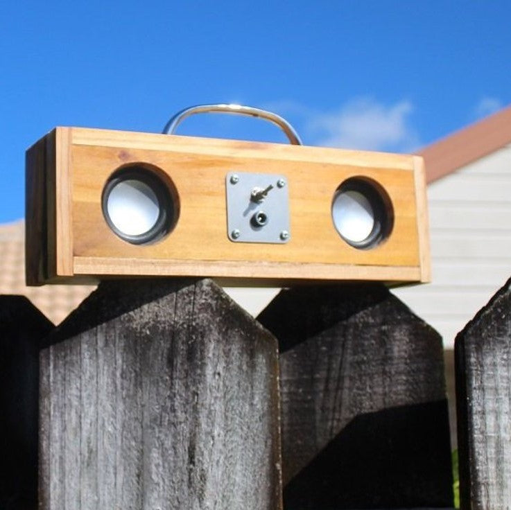 A wooden upcycled speaker with a metal handle.  There are two speakers that look like eyes and a switch in the middle