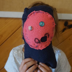 A child with a toy covering their face, obviolsy made by a child but a cute attempt at sewing for a first timer.