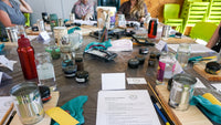 Upcycle Painting Workshop with paint tester pots, brushes, water, tin cans, sand paper all on a table for particpants to practice with.