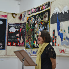 Victoria at a podium presenting her work with refugees.  Behind her are colourful examples of a large collective sewn mural.