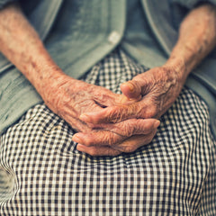 A grandmothers hands resting on her lap