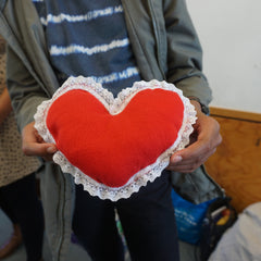 A child holding a red love heart with white ribbon made by hand