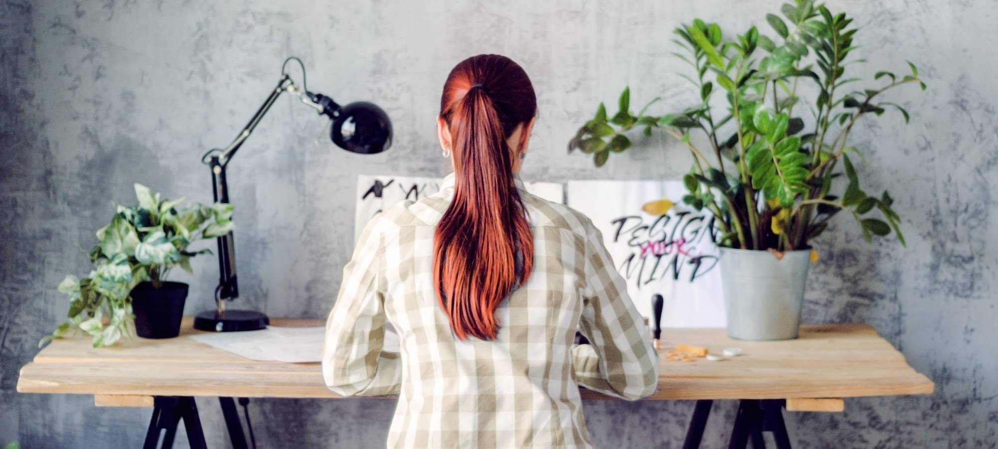 Woman with red hair drawing calligraphy with a desk lamp