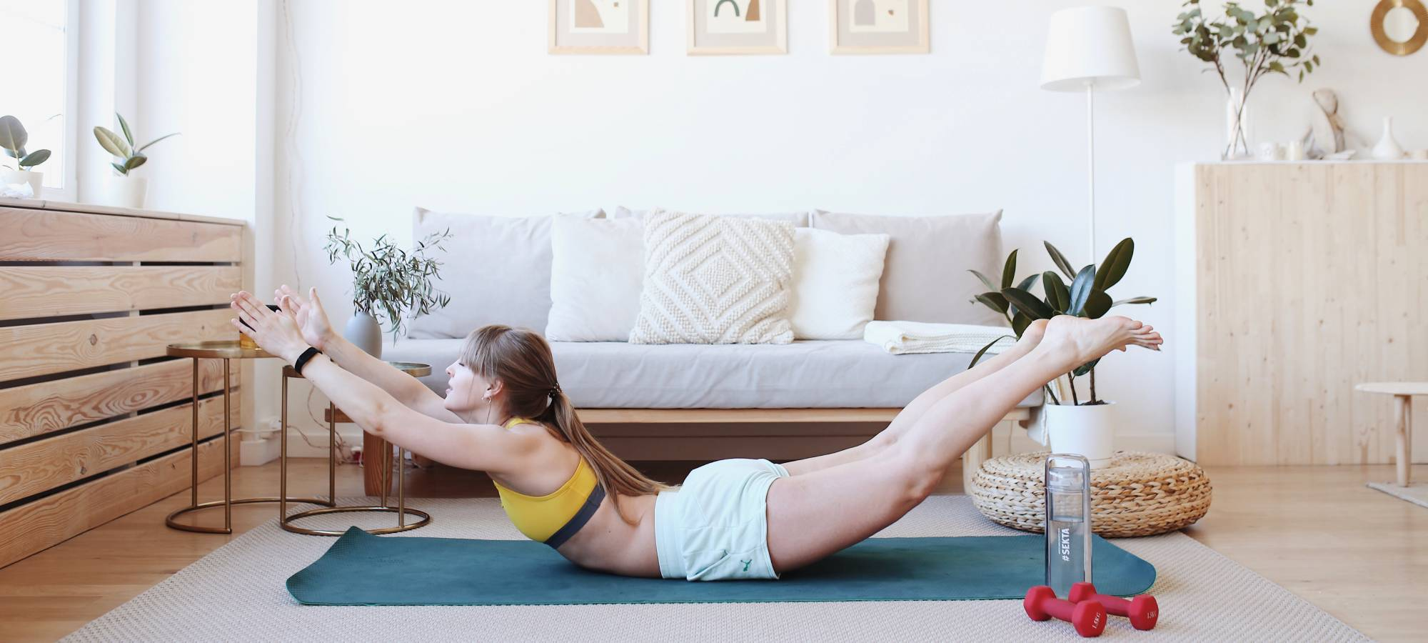 Young fit girl is stretching in yoga at her cozy bright flat
