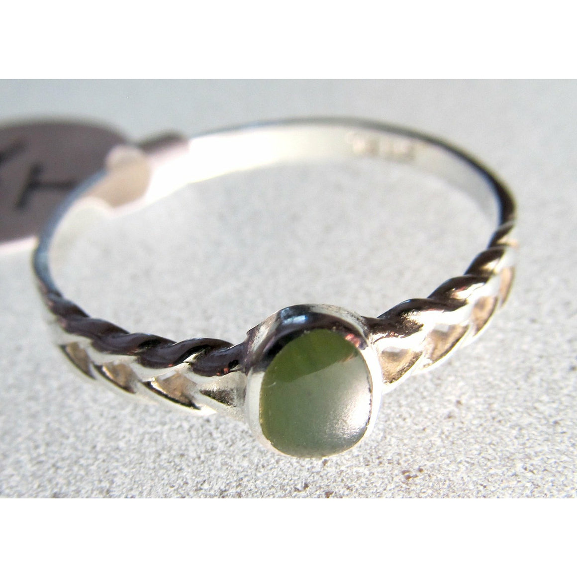 Small oval greenstone inset into patterned sterling silver band