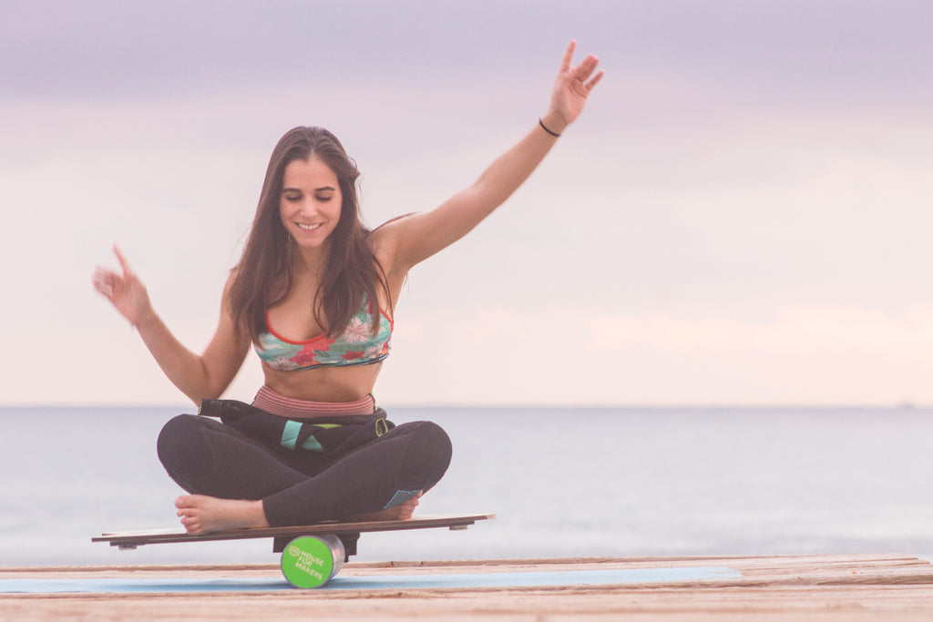 Relaxed woman balancing on a yoga board at the beach