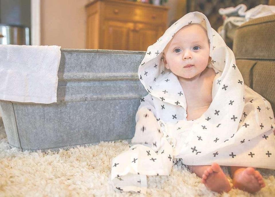 Baby wrapped in white muslin swaddle blanket