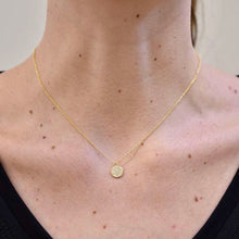 lady is wearing a nine and a half inch gold necklace with one quarter inch diameter gold medallion with crystal accents on front