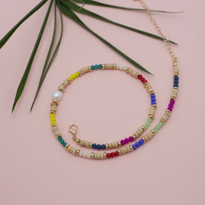 Multi colored beaded necklace with an accent of a centered pearl.