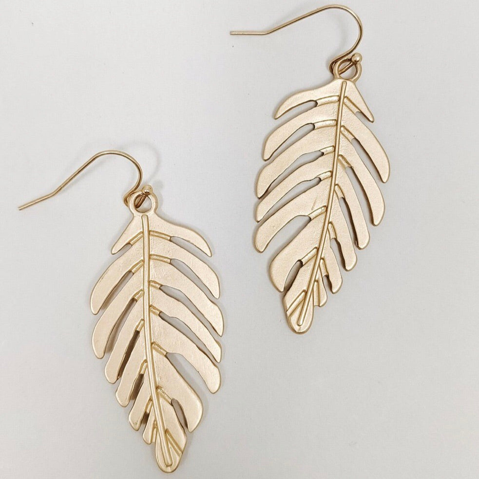 "Leia Earrings-Standout in these gold palm leaves; a tropical breeze favorite! Sweet and attention getting you will be when you pair these with your white flowing maxi and sandals! Gold metal Fish hook backs Sizing - One size | 2"" Long Follow us on Facebook and don't forget to take a look at our New Arrivals!-East Coast She, South Carolina"