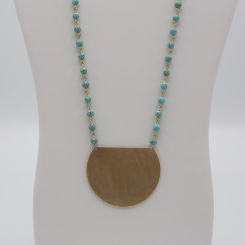 Worn gold metal plate pendant on turquoise beaded stone jewelry necklaces