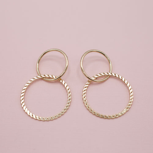 Marjorie Earrings-Two hoops are better than one! The Marjorie Earrings are made with a solid gold round hoop intertwined with another serpentine style round hoop on a post stud back. A fun pair to add to your earring collection! Gold Plated. Stud backs. Follow us on Facebook and don't forget to take a look at our New Arrivals!-East Coast She, South Carolina
