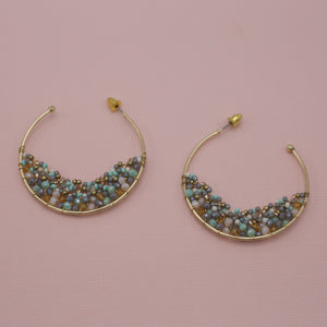 Gold hoops with half moon of gray beads at the bottom of jewelry earrings