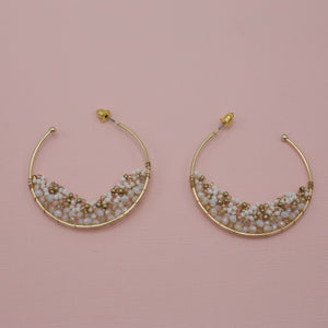 Gold hoops with half moon of ivory beads at the bottom of jewelry earrings