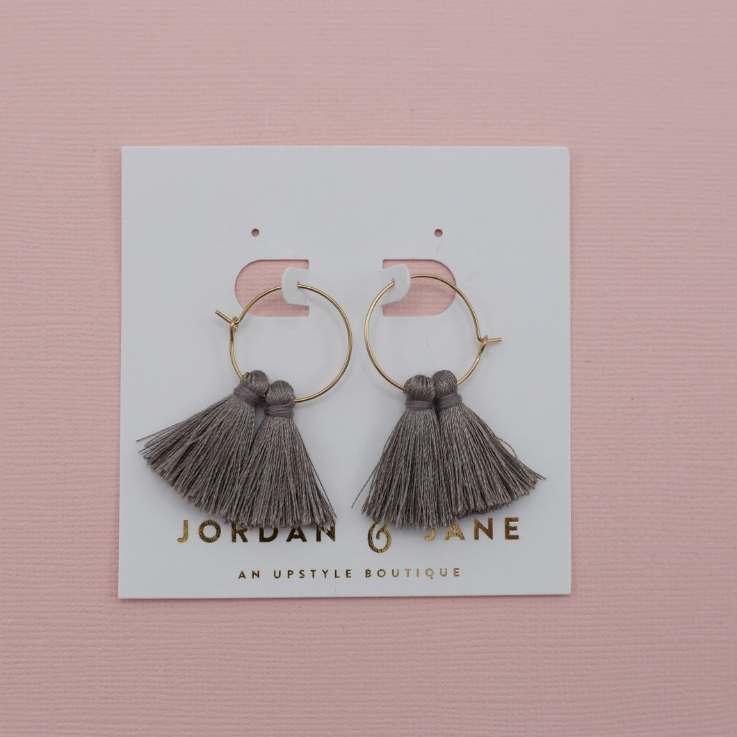 Tiny gold hoop earrings with gray tassels attached