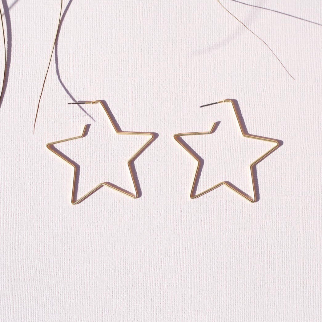 A pair of gold star shaped earrings