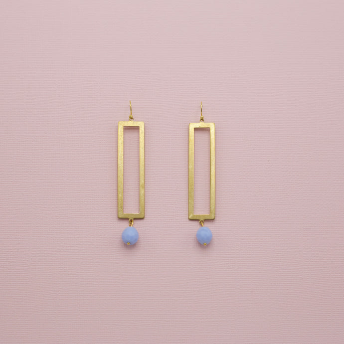 Two and one-quarter inch long gold brass open rectangle earrings with one blue glass ball attached to bottom