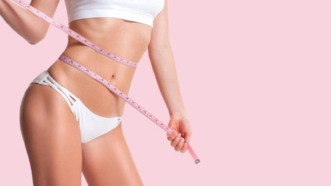 thin woman measuring waist with tape measure