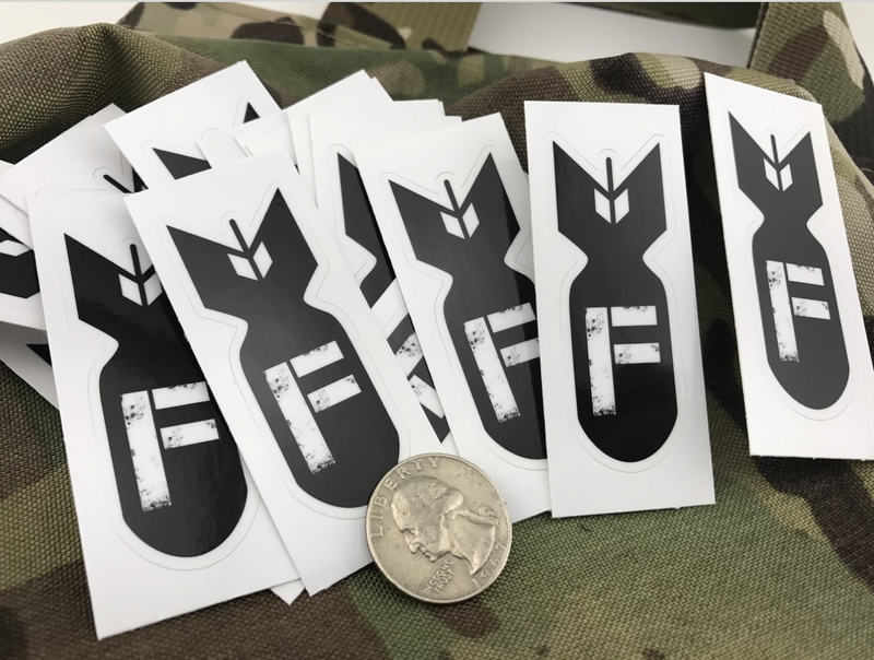 A collection of F Bomb stickers spread over camo fabric, with a quarter for size.