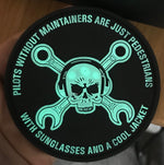 "Glow-in-the-dark view of the Glow in the Dark Maintainer Nation PVC Patch from Challenge Coin Nation with text reading ""Pilots without maintainers are just pedestrians with sunglasses and a cool jacket"""
