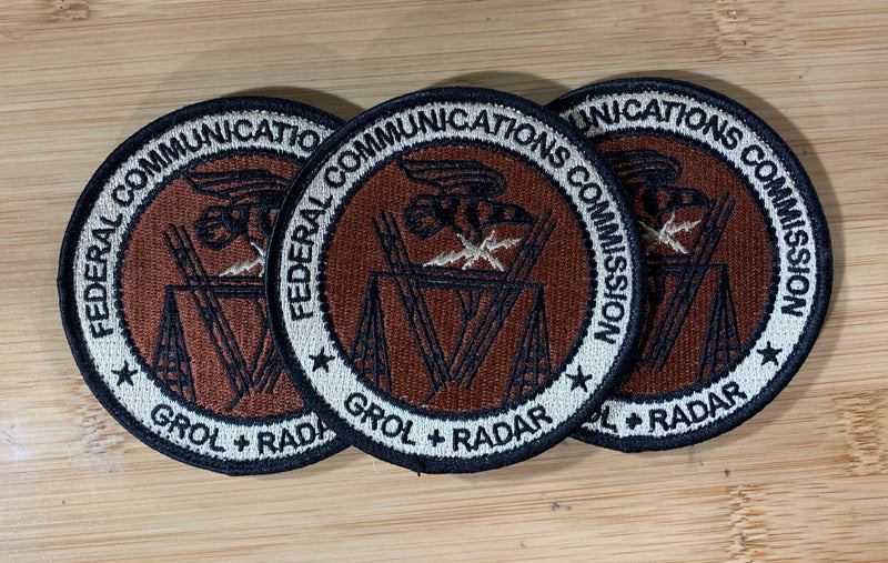 Three embroidered GROL RADAR Patches from Challenge Coin Nation on a wooden surface
